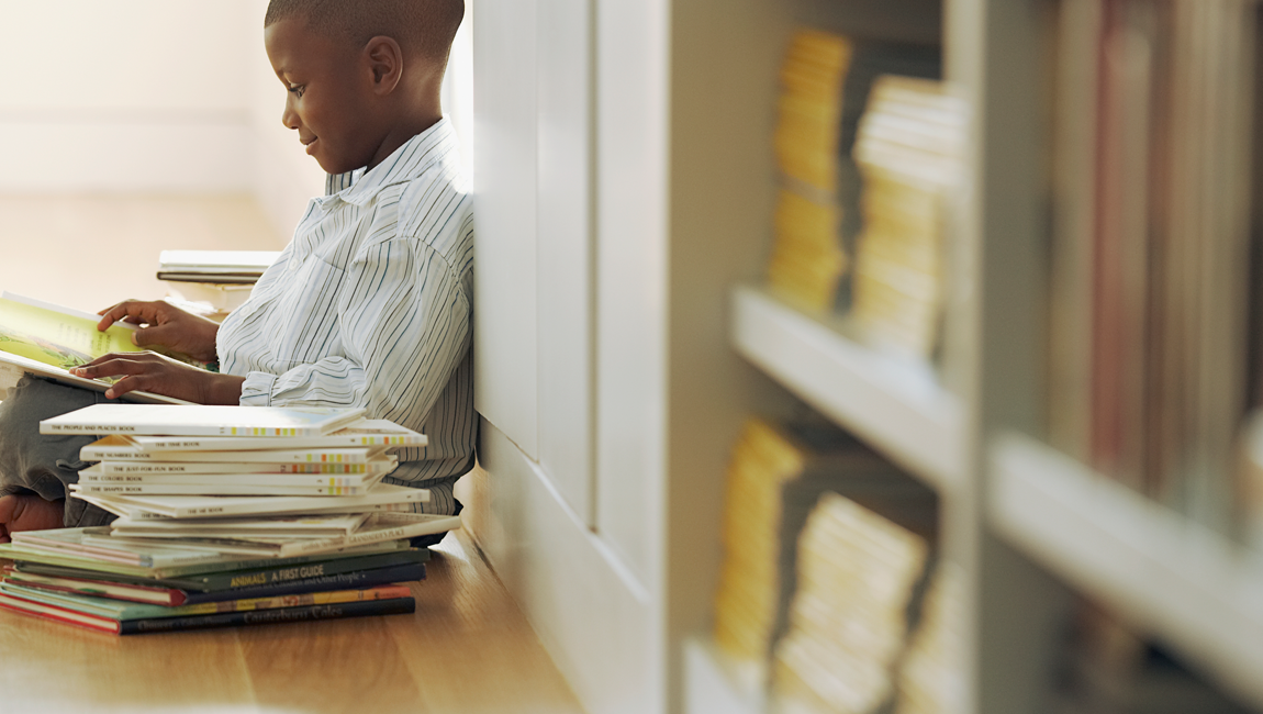 boy sitting in library with books